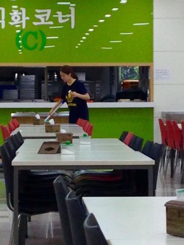 学食で働くお姉さん。掃除をしながら片手にアイス笑