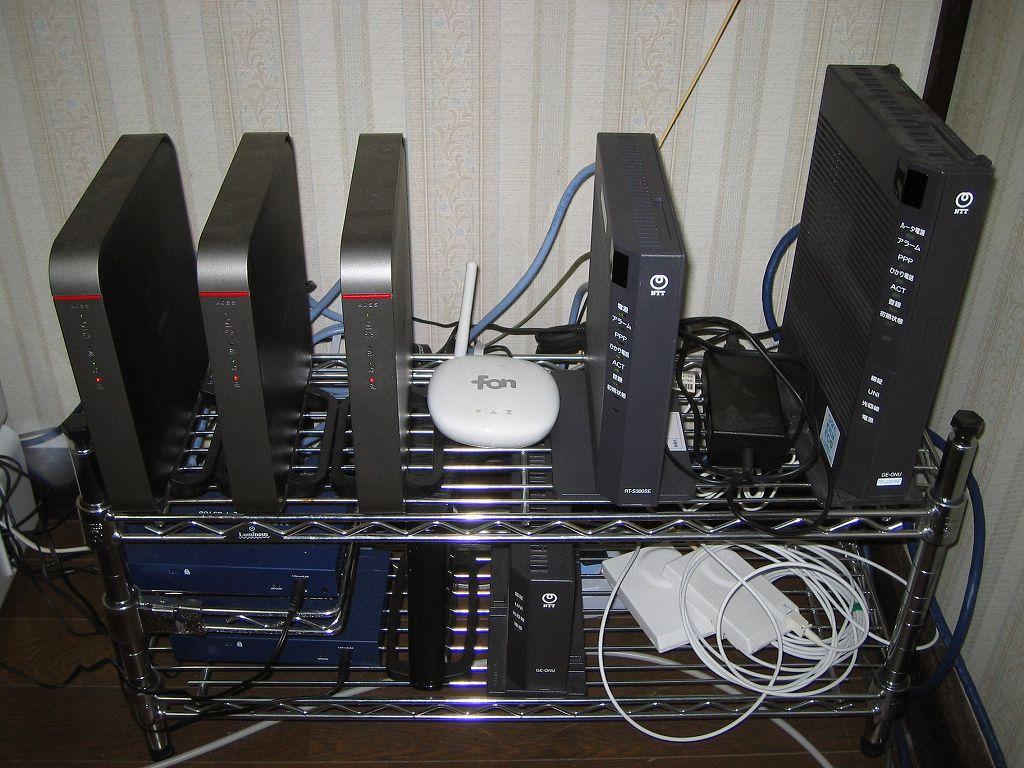 ネットワーク機器設置用メタルラックにブロードバンドルーター、ハブ(HUB)、ひかり電話ルーター、回線終端装置(ONU)、光コンセントを置いたところ