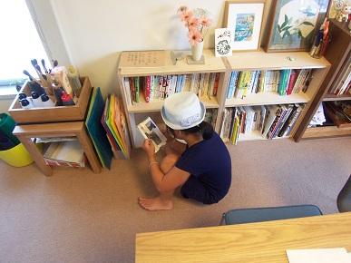 書道教室の小さなライブラリーで本を読む帽子の子