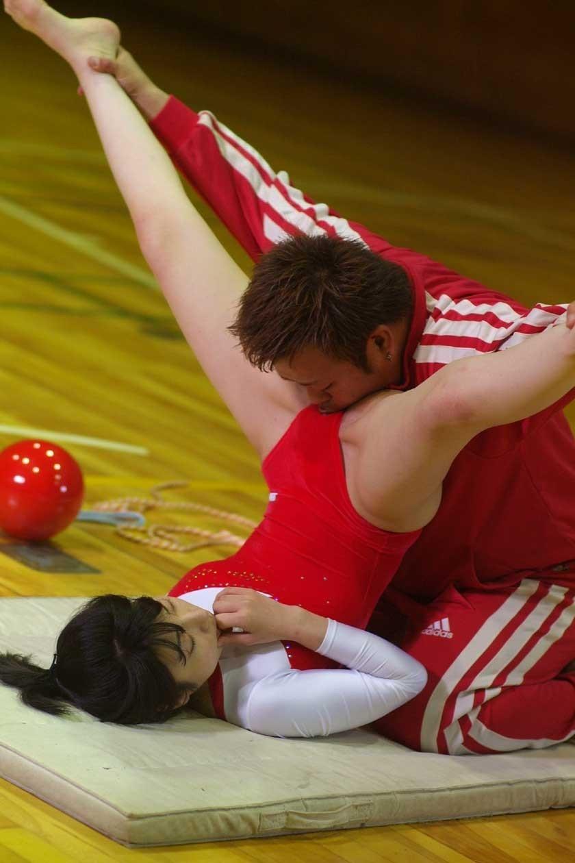 体操で開脚した選手のレオタード股間に口を近づけるコーチ