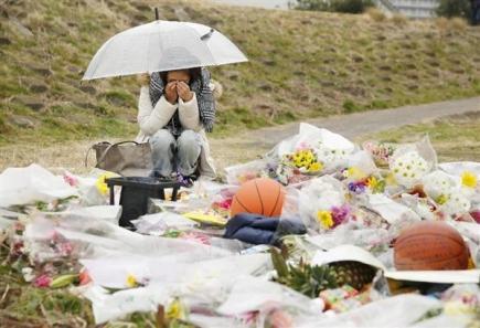 花を供え涙ぐむ女性