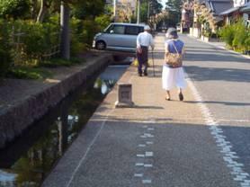 長野県長野市松代の城下の水路の脇を歩く年配の方々をデジカメ写真撮影