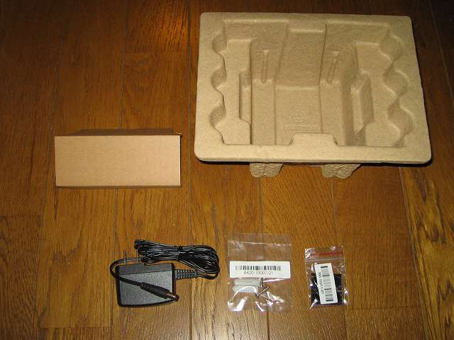 NETGEAR GS108-400JPS(GS108v4) 緩衝材から付属品取り出し、画像左からACアダプター、壁面取付用キット、ゴム足(4個)