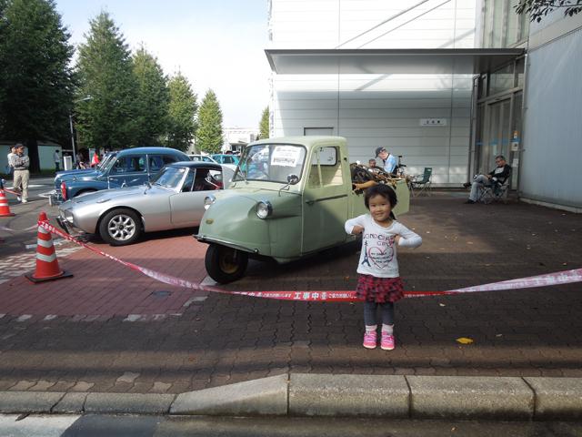 日野自動車のとある建物の前に止ったミゼットと娘